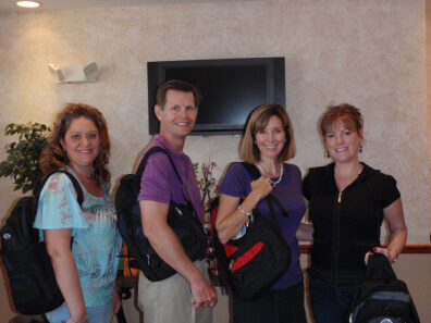 Dunedin FL Dentist Dr. Pitts and his staff model backpacks